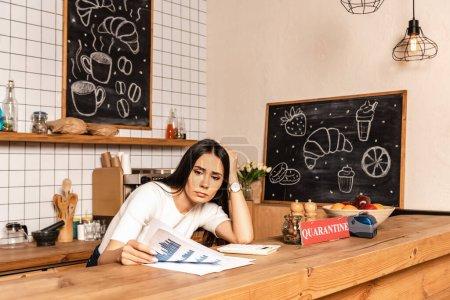 Photo pour Café propriétaire lecture document près de la calculatrice et carte avec lettrage de quarantaine à la table - image libre de droit