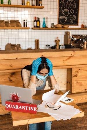 Photo pour Propriétaire de café stressé dans le masque médical en regardant les papiers près de la calculatrice, lunettes, ordinateur portable et carte avec lettrage de quarantaine à table - image libre de droit