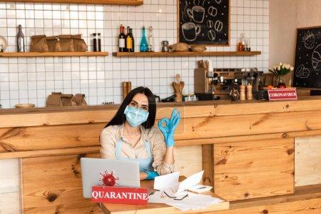 Photo pour Propriétaire de café en masque médical regardant la caméra et montrant signe acceptable près des papiers, ordinateur portable, lunettes et carte avec lettrage de quarantaine à la table - image libre de droit