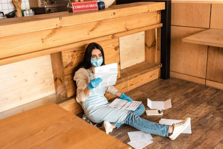 Photo for High angle view of shocked cafe owner in medical mask looking at paper near calculator and table on floor - Royalty Free Image