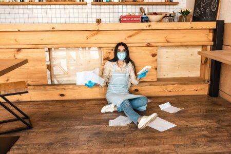 Photo pour Propriétaire de café dans le masque médical tenant des documents avec calculatrice et regardant la caméra près de la table sur le sol - image libre de droit