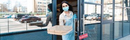 Photo pour Image horizontale du propriétaire du café dans un masque médical près de la porte avec carte avec lettrage de quarantaine montrant les boîtes et regardant la caméra dans la rue - image libre de droit