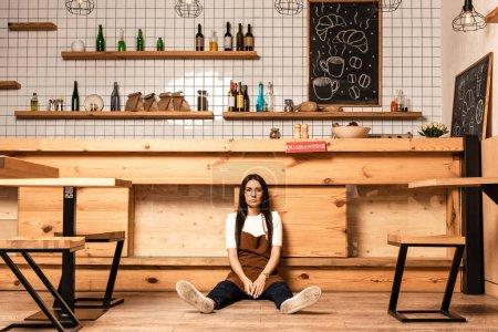 Photo pour Propriétaire de café regardant la caméra et assis au sol près de la table - image libre de droit