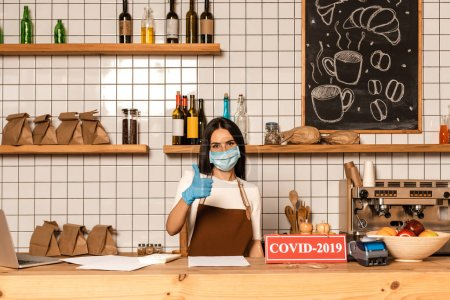 Cafe owner in medical mask showing like sign near table with papers, card with covid-2019 inscription, payment terminal and bowl with fruits