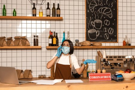 Photo for Cafe owner in medical mask talking on smartphone near table with laptop, papers, payment terminal and bowl with fruits - Royalty Free Image