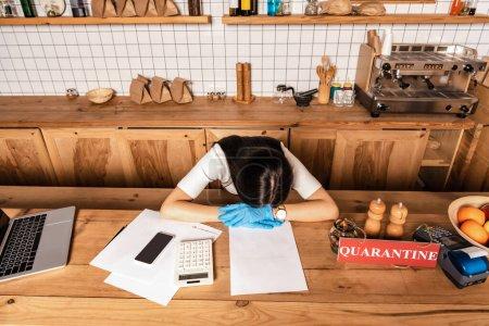 Photo pour Vue grand angle du propriétaire du café avec tête sur les mains à table avec gadgets, papiers, calculatrice, carte avec lettrage de quarantaine et terminal de paiement - image libre de droit