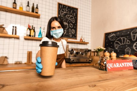 Photo for Selective focus of cafe owner in medical mask showing paper cup of coffee near table with card with quarantine inscription - Royalty Free Image