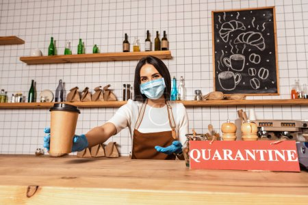 Photo for Cafe owner in medical mask looking at camera and pointing at paper cup of coffee near table with card with quarantine inscription - Royalty Free Image