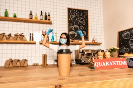 Photo for Selective focus of paper cup of coffee near card with quarantine lettering on table and cafe owner in medical mask with hands in air - Royalty Free Image
