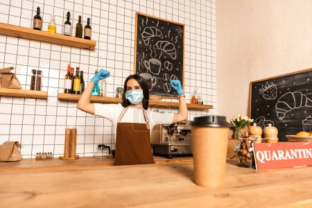 Photo for Selective focus of disposable cup of coffee near card with quarantine lettering on table and cafe owner in medical mask with hands in air - Royalty Free Image