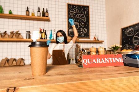 Selektiver Fokus von Einwegbecher Kaffee in der Nähe von Karte mit Quarantäne-Schriftzug auf Tisch und Cafébesitzer in medizinischer Maske mit Hand in Luft