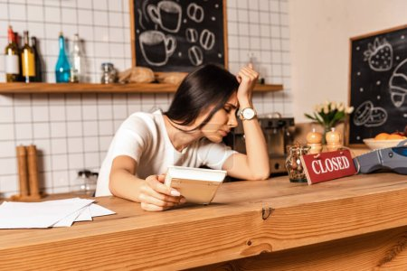 Photo for Upset cafe owner with closed eyes holding calculator and leaning on table with papers and card with closed inscription - Royalty Free Image