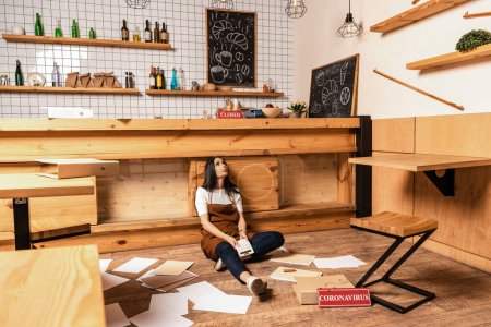 Cafe owner with calculator sitting near table, papers and card with quarantine lettering on floor