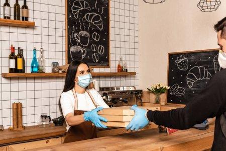 Photo pour Le propriétaire d'un café en masque médical remet des boîtes à un messager près de la table - image libre de droit