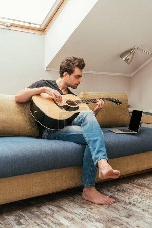 Photo pour Jeune homme attentif jouant de la guitare assis sur un canapé près d'un ordinateur portable avec écran vierge - image libre de droit