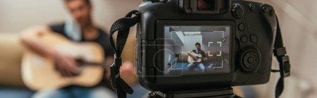 Foto de Enfoque selectivo de jóvenes vlogger tocando guitarra mientras se mira la cámara digital, imagen horizontal. - Imagen libre de derechos