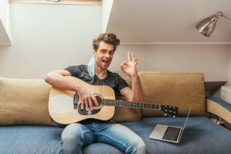 Photo pour Homme excité avec masque médical à l'oreille tenant la guitare et montrant signe rock tout en étant assis sur le canapé près de l'ordinateur portable - image libre de droit