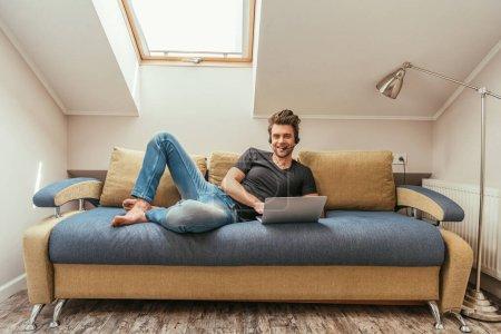 Photo pour Gai homme en casque d'écoute allongé sur un canapé près d'un ordinateur portable et regardant la caméra - image libre de droit
