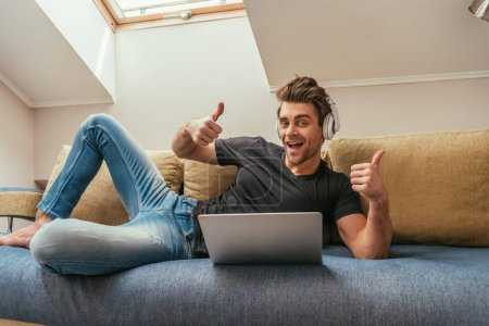 happy man in wireless headphones showing thumbs up while lying on sofa near laptop