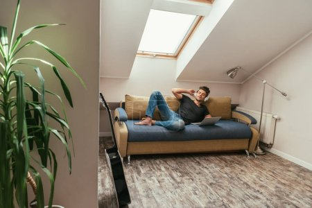 Photo for Young man listening music in wireless headphones while lying on sofa near laptop in attic room - Royalty Free Image