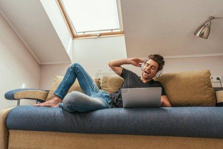 Photo pour Homme excité écouter de la musique dans les écouteurs sans fil tout en étant couché sur le canapé près d'un ordinateur portable - image libre de droit