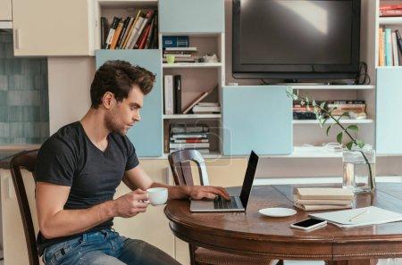 Photo pour Vue latérale de l'homme réfléchi tenant tasse de café tout en travaillant à l'ordinateur portable dans la cuisine - image libre de droit