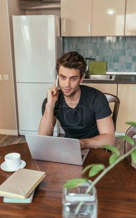 Photo pour Foyer sélectif de l'homme sérieux parlant sur smartphone près d'un ordinateur portable tout en travaillant dans la cuisine - image libre de droit