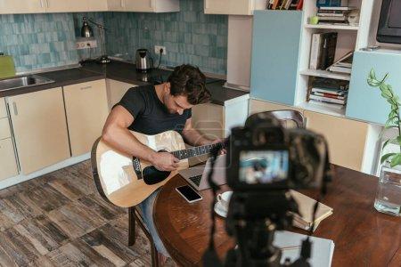 Photo pour Vue grand angle du jeune vlogger jouant de la guitare dans la cuisine près de l'appareil photo numérique sur trépied - image libre de droit