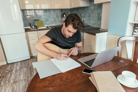Photo pour Vue grand angle de jeune homme attentif avec écriture de guitare sur papier tout en étant assis près d'un ordinateur portable - image libre de droit