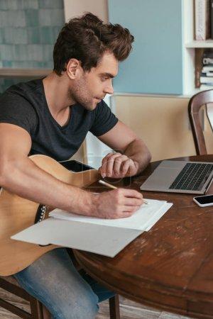 Photo pour Jeune homme concentré avec des notes d'écriture de guitare tout en regardant ordinateur portable - image libre de droit