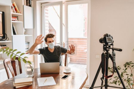 young video blogger in medical mask gesturing while looking at digital camera on tripod