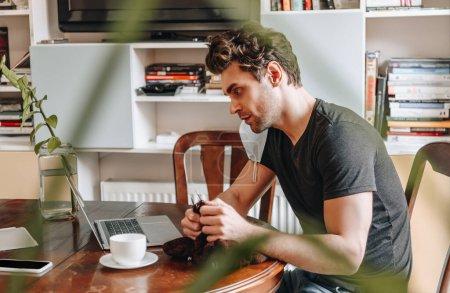 Photo pour Vue latérale du jeune homme concentré regardant l'ordinateur portable tout en tricotant à la maison - image libre de droit