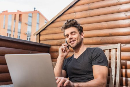 Photo for Handsome man using laptop and talking on smartphone while sitting on balcony and smiling at camera - Royalty Free Image