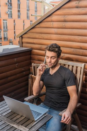 Photo for Young, skeptical man using laptop and talking on smartphone while sitting on balcony - Royalty Free Image
