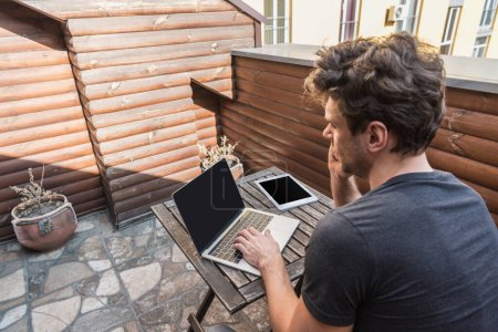 Photo for Young man using laptop with blank screen near digital tablet while sitting on balcony - Royalty Free Image