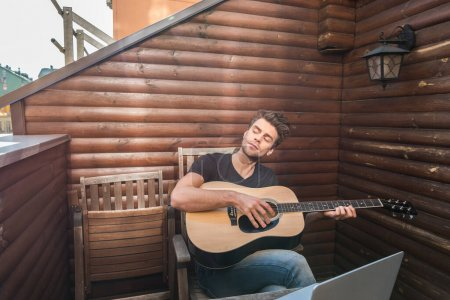 Photo pour Homme rêveur jouer de la guitare tout en étant assis sur le balcon près d'un ordinateur portable - image libre de droit