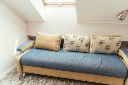 Photo pour Confortable chambre mansardée avec fenêtre et confortable canapé avec oreillers - image libre de droit