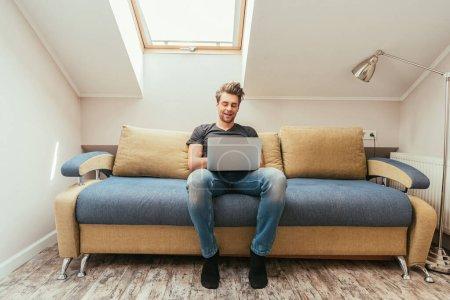Photo pour Un jeune homme souriant sur un ordinateur portable assis sur un canapé à la maison - image libre de droit