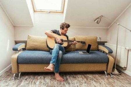 Photo pour Jeune homme jouant de la guitare assis sur un canapé et regardant un ordinateur portatif à écran vierge - image libre de droit