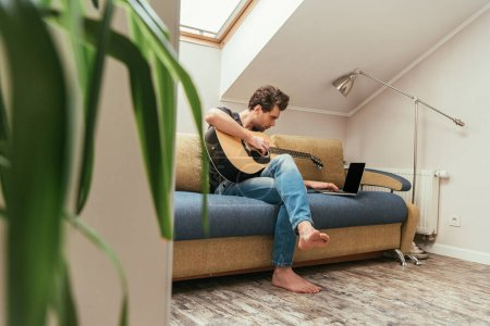 selective focus of young man playing guitar while sitting on sofa near laptop with blank screen