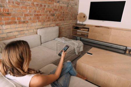 Photo pour Fille tenant télécommande et regarder la télévision avec écran blanc pendant l'auto-isolement, mise au point sélective - image libre de droit