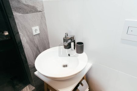 modern interior of bathroom with white washbasin and soap dispenser
