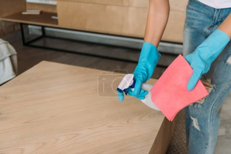 Photo for Cropped view of girl in rubber gloves cleaning table with rag and antiseptic spray during quarantine - Royalty Free Image