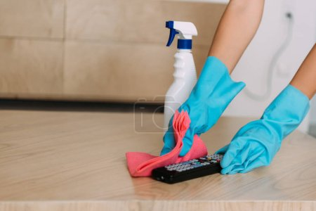 Photo for Cropped view of woman in rubber gloves cleaning remote controller with rag and antiseptic spray during quarantine - Royalty Free Image