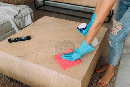 Photo pour Vue recadrée de la femme en gants de caoutchouc table de nettoyage avec chiffon et vaporisateur pendant la quarantaine - image libre de droit