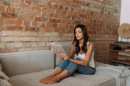 Photo pour Attrayant livre de lecture fille sur canapé pendant l'isolement personnel - image libre de droit