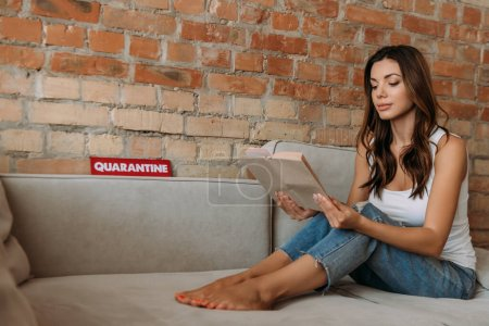 beautiful woman reading book on sofa with quarantine sign during self isolation