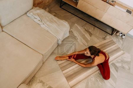 Photo for Beautiful woman stretching on yoga mat at home on quarantine, overhead view - Royalty Free Image