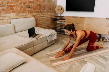 Photo for Attractive girl stretching online with laptop on yoga mat at home on self isolation - Royalty Free Image