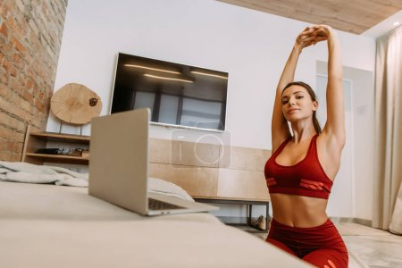 beautiful sportswoman training online and stretching at home during quarantine